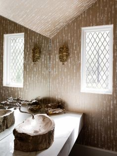 With gold leaf-inspired wall art and metallic wallpaper mimicking the look of bark, this bathroom embraces nature in a glamorous way. A tree trunk sink completes the rustic glam look.