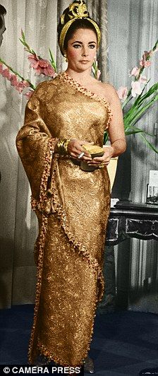 Golden girl: Elizabeth Taylor in Balenciaga.. a sari gown by Balenciaga that has a guide price of £30,000 to £50,000. She points out a concealed corset that would have drawn the star's waist in by a crucial two inches — when she wore this gown, in 1964, Liz Taylor had a 24-inch waist and a 37-inch bust. Kerry has a photo taken of Taylor in the Balenciaga gown, her hair in a plait, carrying a gold clutch and golden shoes to match..