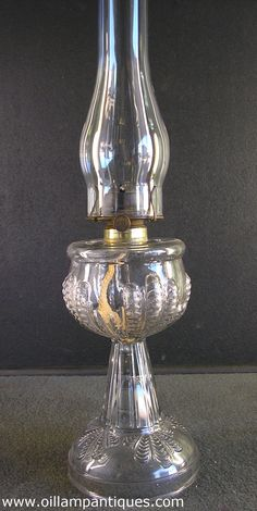 This clear glass Turkey Foot oil lamp is a fine example of the early machine made glass products. It was made in the first part of the 20th century by The United States Glass Company