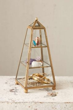 A glass tower for storing jewelry.