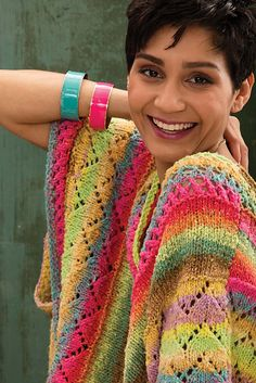 Lacy bands in dazzling yellow, lime and fuchsia make the essential blanket poncho ready for warmer climes. The front and back are knit side to side in Taiyo colorway #75, alternating panels of eyelet mesh, stockinette and zig zag lace that are divided by purl ridges. Bound-off and cast-on sections create the mirrored deep V-neckline. The shoulders and sides are seamed to form deep armholes.