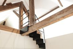 A black spiral staircase clips onto exposed timber beams in the roof structure…