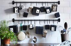 Valkoisilla laatoilla laatoitettu keittiönseinä, jossa mustat tangot. Normaalisti tangoille on ripustettu keittiövälineitä, mutta nyt keittiövälineet on laitettu työtasolle ruukkuun ja tangoille on ripustettu mustia lahjarasioita joulukalenteriksi.