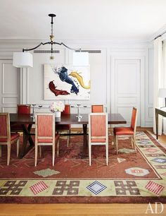 A James Nares painting hangs in the dining room, which is outfitted with a Jean-Michel Frank table from BAC | archdigest.com