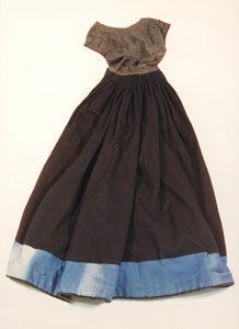 Der Kleiderrock mit angenähtem Mieder ist aus schwarz-blauem Tuch mit farbigem Besatz und rosa-kariertem Futter. Er gehört zur Frauen-Festtracht, die um 1900 auf Föhr, Amrum und den Halligen getragen wurde.