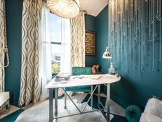 Drawing inspiration from the unfolding ocean views, designer Laura Larkin paired a velvety, saturated wall color with cascading crystal baubles and wavy-print drapery in the San Francisco Decorator Showcase 2014 woman's office.