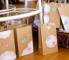 Bolsitas de papel decoradas con blondasPara dar detallitos a los invitados utilizaron estas bolsas de papel Kraft decoradas con pequeñas blondas, collaritos de perlas, mariposas decorativas y flores.