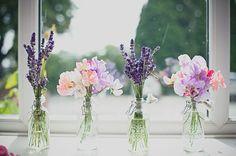 Stop leuk gekleurde veldbloemetjes in vaasjes als decoratie.