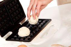 Duw het deeg voor luikse wafels in het wafelijzer alvorens te bakken