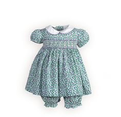 Purple Posies Hand-Smocked Newborn Girls Dress Green vines with purple flowers splashed against a white background create the perfect summer dress. Exquisite hand smocked bodice. High-waist cotton dress has white split piqué collar piped in lilac. Button back with tie back sash.
