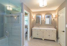 Master Bathroom designed by KHL Design Studio. Herringbone tile floor, shower niche, chevron detail mirrors, flush-mount lighting.