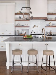 Chic kitchen features an iron lantern over a white center island with legs topped with a soapstone ...