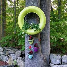 Repurposed tires , spray painted and turned into planters then hung on a tree