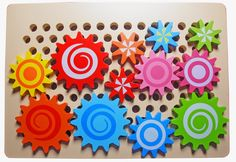 Wooden Gears Peg Board. Fixing the shafts to the gears eliminates eye-poking hazards on vertical pegboard.