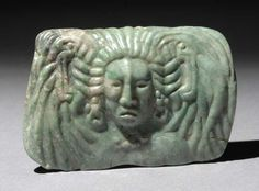 Maya. Jade pendant. Realistic full face portrait of dignitary wearing feather headdress. Style of carving suggests terminal classic period. 7 cm wide 4.8 cm high.