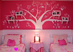 This is cool decor for a girl's shared room. Love the tree painted on the wall with the names hanging from it and the picture frame shelves attached to the tree branches.