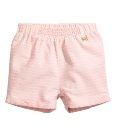 Powder pink. Shorts in soft, woven cotton fabric. Elasticized waistband with decorative smocking at center front, decorative butterfly-shaped metal button
