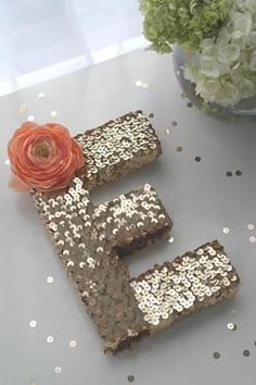 wedding monogram covered with gold sequins and coral colored flower @myweddingdotcom