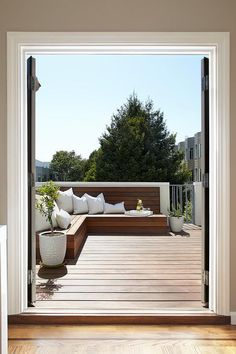 Double doors open to a stained deck boasting a L shaped built-in teak bench adorned with white outdoor pillows alongside plants in white planters. Deck Seating, Backyard Seating, Built In Seating, Built In Bench, Outdoor Seating, Backyard Patio, Deck Benches, Built In Bbq, Back Garden Design