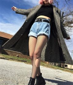 Knitted coat with black crop top, denim shorts, ripped fishnet tights & boots