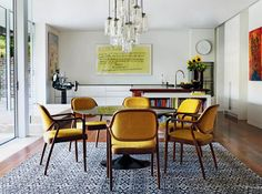 yellow dining chairs eclectic dining room, black tulip table