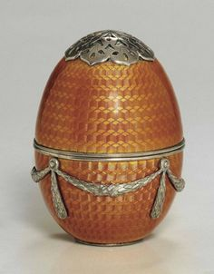 A PARCEL-GILT SILVER AND GUILLOCHÉ ENAMEL EGG SANDER   MARKED FABERGÉ, WITH THE WORKMASTER'S MARK OF MICHAEL PERCHIN, ST. PETERSBURG, CIRCA 1890  Ovoid, enameled overall in translucent orange over a basket-weave guilloché ground, the lower half applied with chased and engraved ribbon-tied laurel swags, the screw cover with openwork swivel cap, with gilt interior, marked under base