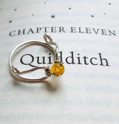 This beautiful minimalist ring makes a wonderful gift for any Harry Potter fan! A genuine semi-precious Citrine bead sits in the middle of two wire wrapped wings, creating a simple and sleek design. The wire band is nickle free, sterling silver plated, and can be ordered in most sizes.