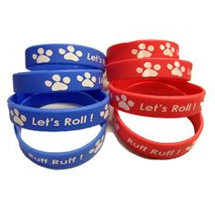 """These fun favors are perfect for any Paw Patrol, Dog, Puppy, or Animal theme birthday party. Wristbands are blue and red with a white print """"Let's Roll"""" and """"Ruff Ruff"""". Youth size to fit those small"""