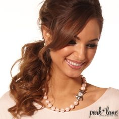 Kate Necklace  Simple, pink faux pearl earring studs are the perfect accompaniment for designer-inspired KATE necklace. The single strand of large, lustrous soft pink glass pearls is fastened by a silver bow accented with crystals. Wear it in front, back, or to the side. The double-strand glass pearl bracelet elevates your outfit. You'll look polished and sophisticated wearing KATE! Kate Complements: Rose Garden bracelet; Lola ring
