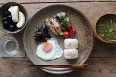 Washoku breakfast.  Fried egg, stewed hijiki seaweed, sauteed enoki mushrooms + broccoli, sauteed mini-tomatoes, omusubi rice balls with toasted sesami, daikon miso soup, with asian pear + grapes.