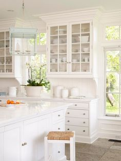 White Kitchen with blue lantern. Crushing on these glass front cabinets.
