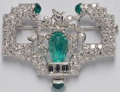 Art Deco Platinum, Emerald and Diamond Brooch, Marcus & Co., set with a pear-shape fancy-cut emerald, fruther bead-set with baguette and transitional-cut diamonds, approx. total diamond wt. 3.60 cts., three cabochon emerald highlights, wd. 1 3/4 in., signed Marcus & Co.   Via Skinner.
