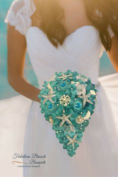 This bridal beach bouquet features starfish, brooches, shells, and pearls on a bed of blue/green flowers or white roses. The handle is finished with satin ribbon in the color of your choice. It is per