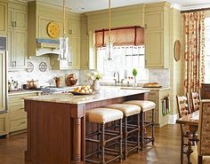 cabinets are painted a light green-gold with a distressed finish for a timeworn  effect. The island is equipped with three barstools upholstered with leather  seats. The stools' turned legs and island's support posts bring elements of the  adjoining family and dining rooms into the kitchen, complete with the island's  warm wood finish