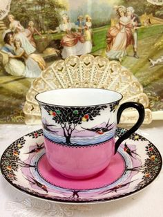 Shelley demitasse cup and saucer Pink base with swallows flying in trees.