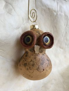 """A decorative owl ornament, on a gold hanger, fashioned from a small 3"""" gourd by Jennifer Rapaich of the Menominee tribe."""