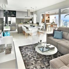 Belíssimo apartamento com integração de estar jantar e cozinha. A base é neutra em tons de cinza e branco. E foram usadas pitadas de azul claro, cor tendência no decor. Decoração salas integradas