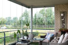 Gezellig ingericht balkon met flexibele balkonbeglazing om het