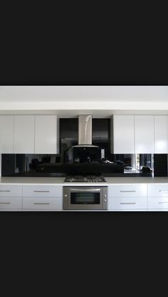 Ice white cabinets with polished black glass splashback and stainless steel appliances. Kitchen Splashback Designs, White Kitchen Backsplash, Glass Kitchen, Kitchen Design, Glass Splashbacks, Kitchen Colour Schemes, Kitchen Colors, Kitchen Interior, Kitchen Decor