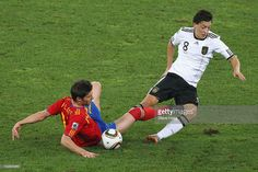 Xabi Alonso of Spain and Mesut Oezil of Germany battle for the ball during the 2010 FIFA World Cup South Africa Semi Final match between Germany and Spain at Durban Stadium on July 7, 2010 in Durban, South Africa.