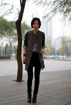 Tang Shuang is a senior fashion editor at Outlook Magazine in Shanghai. She is wearing a striped menswear inspired shirt under her leather-sleeve coat.  --Beijing Street Style
