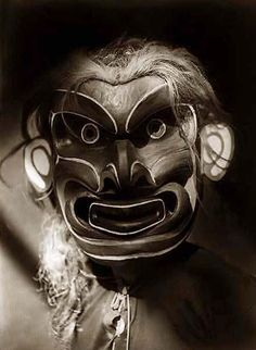 Image of Pgwis. It was taken in 1914 by Edward S. Curtis. The image shows Kwakiutl person wearing mask of mythical creature Pgwis (man of the sea).