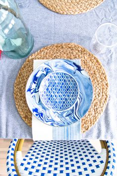 www.pencilshavingsstudio.com Blue tablescape setting with mix and match patterns. Raffia round placemats with blue marbleized enamel plates and Aerin for Williams Sonoma dishes.
