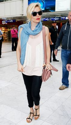 Sienna Miller wears Prada sandals with an ivory top and a rose leather purse. She accessorizes with a light blue scarf and tortoiseshell sunglasses.