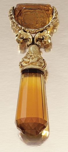GOLD AND CITRINE DESK SEAL, CIRCA 1820.  The tapered faceted citrine handle, to a gold work mount of foliate, scroll and shell design, terminating on a three faced carved citrine seal, two faces engraved with a coats-of-arms.