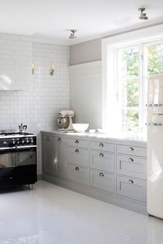light grey cabinets, marble countertops, subway tiles.