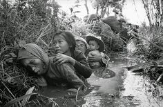 Women and children crouch in a muddy canal as they take cover from intense Viet Cong fire at Bao Trai, about 20 miles west of Saigon, on January 1, 1966. Paratroopers, background, of the U.S. 173rd Airborne Brigade escorted the South Vietnamese civilians through a series of firefights during the U.S. assault on a Viet Cong stronghold. (Horst Faas/AP)