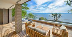 """Die Holzterrasse vor dem Schlafzimmer ermöglicht, dank eines Glas-Balkongeländers in jeder (Sitz-)Höhe einen uneingeschränkten Blick über den Bodensee – Baufritz Musterhaus """"Haus am See"""""""