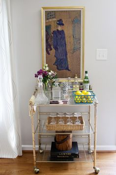 Gold bar cart - fresh flowers, fresh lemons, glasses. Gold framed painting behind - classic artwork that the art uses colours from.
