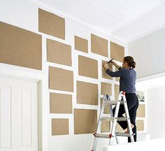 experiment with photo wall arrangements without harming the walls -- paper and painter's tape.